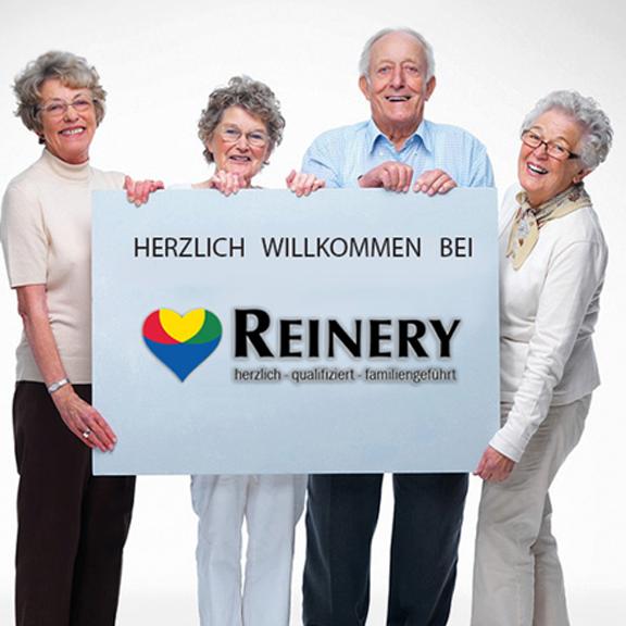 Vier Senioren halten ein Schild mit dem Schriftzug Herzlich Willkommen bei Reinery