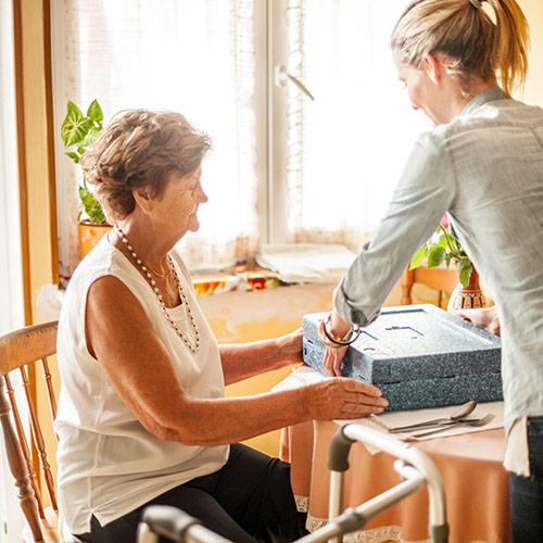 Pflegerin bringt Dame in der Tagespflege etwas zu Essen