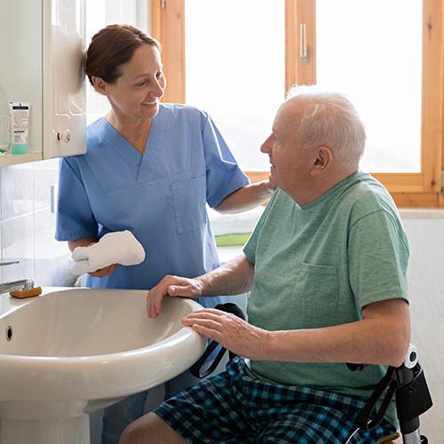 Pflegerin kümmert sich um älteren Herren in der 24 Stunden Intensivpflege