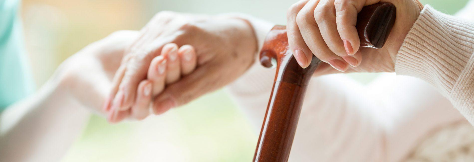 Pflegerin hilft einer Dame mit Gehstock aufzustehen